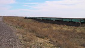 A train on a desert. A scenic shot of a train running on a desert stock footage