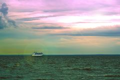 Scenic sky sunset with a cruise ship sailing away on horizon with green grass on foreground. Vacation conception.  Stock Photo