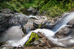 Scenic small waterfall at north in Thailand. Stream flowing over the rock in the forest Royalty Free Stock Image