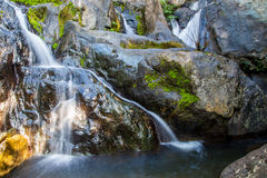 Scenic small waterfall at north in Thailand. Stream flowing over the rock in the forest Stock Image