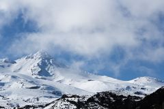 Scenic snow mountain partially covered by mists with blue sky in the background. stock photo