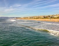 Scenic Southern California with beachfront homes on the Strand and waves rolling in. Southern California beach scene with Pacific Ocean waves rolling in, people Royalty Free Stock Photography