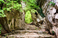 Scenic stone stairs leading up to gate in rocks Stock Photos
