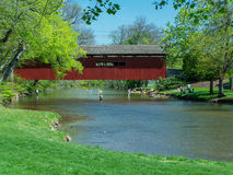 Scenic Stream - Covered Bridge - Summer Activities. Covered bridge sets the site for people enjoying some picnicking, fishing, kayaking, and swimming. Taken on Royalty Free Stock Photos