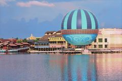 Scenic summer sunset view of Lake Buena Vista pier with color buildings, air balloon and boats