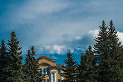 Scenic sunny sky with brights clouds with eastern pines and antic building in Saint Petersburg botanical garden public property. Scenic sunny sky with brights Stock Images
