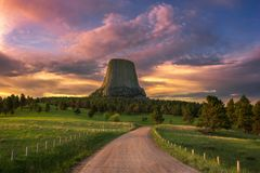 Scenic sunrise over Wyoming`s Devils Tower National monument. Warm sunset light filters across a meadow and gravel road below the Devils Tower Monument in stock images
