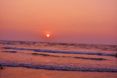 Sunset with sea water at Morjim Beach, Goa. Scenic sunset at Morjim beach, Goa, India. It is located in North Goa. Morjim is famous as the nesting ground of the stock images