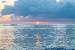 Scenic sunset off the coast of tropical Caribbean island. Sun just above the horizon. royalty free stock photo