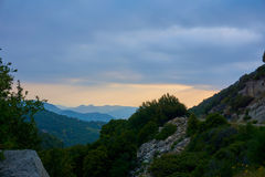 Scenic sunset over green blooming hill landscape. With view on a road royalty free stock images