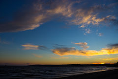 Scenic sunset over ocean beach Stock Photo
