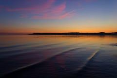 Scenic sunset over ocean beach Stock Images