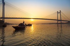 Scenic sunset over Vidyasagar bridge with wooden boats on river Hooghly, Kolkata, India. A Silhouette sunset view of a wooden boats on the Hooghly river bank royalty free stock photos