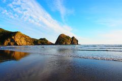 Stunning view of Piha beach, New Zealand north island. Scenic sunset at piha beach with rock formations at the background royalty free stock photography