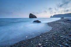 Scenic sunset on a rocky seashore on long exposure Stock Image
