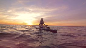 Scenic sunset view with a young woman on a paddleboard. 4K stock footage