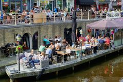 People have fun  at modern lounge terraces along a canal,Leeuwarden,Netherlands Stock Photo