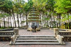 Scenic tower and urn for burning incense, Thien Mu Pagoda. Scenic tower and black urn for burning incense among green trees at the Pagoda of the Celestial Lady ( stock image