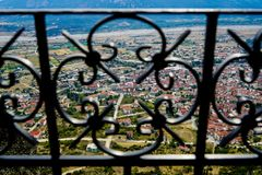 Scenic townscape view of ancient red roof buildings, urban street and space in Kalambaka from Meteora monasteries rock. Through wrought iron rail foreground stock images