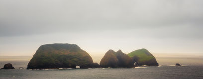 Scenic tranquil Three Arch Rocks on the Oregon Coast. Three Arch Rocks sit under moody sky of low clouds, misty sky and sunlit water creating a a soft tranquil royalty free stock photo