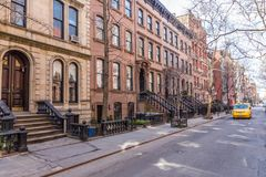 Scenic tree lined street of historic brownstone buildings in the West Village neighborhood of Manhattan in New York City. NYC USA. Traditional yellow taxi car royalty free stock photo