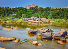 Scenic Tungabhadra River bank in Hampi, India. Landscape with unique mountain formation with amazing stones, water and palm trees Stock Images