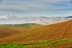 Landscape of San Quirico d`Orcia, Tuscany, Italy. Scenic Tuscan landscape with beautiful fields, meadows and hills with morning fogs. San Quirico d`Orcia Stock Photos