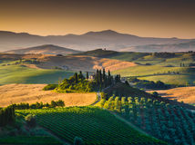 Scenic Tuscany landscape with rolling hills and valleys at sunset Stock Photos