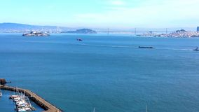 Cityscape-the Bay Bridge. Scenic view across the bay . Anchored sailboats in harbor while across the waters is alcatraz,  the bay bridge and San Francisco. A Royalty Free Stock Image