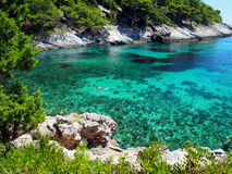 Scenic view of Adriatic sea bay. Man swimming in bright, blue sea. Photo taken on: July 2016 Royalty Free Stock Images