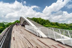 Bridge imitating wave. Wooden walkway leading to park, Singapore. Scenic view of amazing bridge imitating a wave. Fantastical shape of the pedestrian bridge in Royalty Free Stock Photography