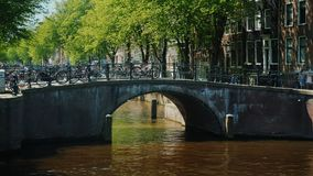 The scenic view of Amsterdam is the bridge over the canal, where many bicycles are parked. A typical picture in the city. A scenic view of Amsterdam - a bridge stock video