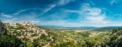 Scenic view of ancient hilltop village of Gordes in Provence, Fr. Amazing panorama scenic view of medieval hilltop village of Gordes in Provence, France. Blue Stock Photography