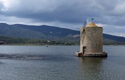 Scenic view of the ancient Spanish windmill in the Orbetello lagoon, royalty free stock image