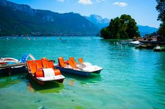 Scenic view of Annecy lake and pedalo with swan island in background in France during summer day royalty free stock photography