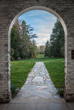Scenic View through Archway. Brick archway framing flagstone path and scenery of trees, grass and sky Stock Photo
