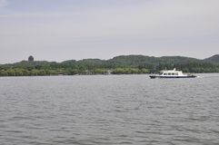 Scenic view area from the famous West Lake in Hangzhou. Scenic view area with a cruise white vessel on the West Lake in Hangzhou China on 3rd may 2018 stock photos