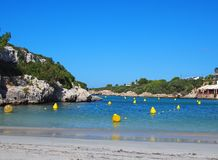 View of the beach and bay at Cala Santandria in Menorca with yellow boat markers in a bright blue sunlit sea and surroundin royalty free stock photos