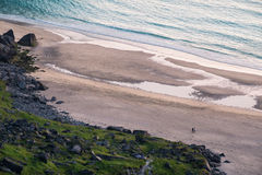 Scenic view from the beach with a couple walking at summer evening Stock Image