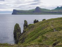 Scenic view on beautiful Hornbjarg cliffs in west fjords, remote nature reserve Hornstrandir in Iceland, with big bird cliff rocks. Blue sea and cloudy sky stock image