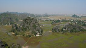 Scenic view of beautiful karst scenery and rice paddy fields. Scenic view of beautiful karst scenery, river and rice paddy fields seen from above at Tam Coc stock footage