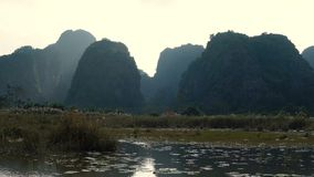 Scenic view of beautiful karst scenery, wetlands. Seen from the boat at Van Long Nature Reserve, Vietnam. Tourists traveling in small boat in tranquil landscape stock footage