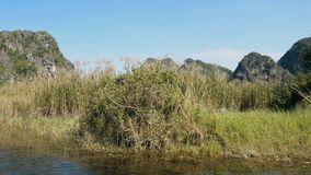 Scenic view of beautiful karst scenery, wetlands. Seen from the boat at Van Long Nature Reserve, Vietnam. Tourists traveling in small boat in tranquil landscape stock video