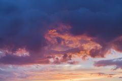 Scenic view of beautiful sunset, vibrant golden and purple clouds, evening sky. Natural background, art shades Royalty Free Stock Image