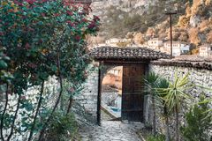 Scenic view in Berat. Berat, historic city in the south of Albania, view to the city through an opened old wooden door. Private garden, gates, stone walls and a Stock Photos