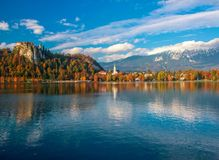 Scenic view of Bled lake at sunny autumn day. With castle rock and St Martin church under beautiful sky reflected in lake water royalty free stock photos