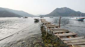 Scenic view of boats at sea bay, old wooden pier in the water, and low mountains on the background. Turkey.  stock video footage