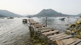 Scenic view of boats at sea bay, old wooden pier in the water, and low mountains on the background. Turkey.  stock footage