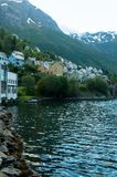 Scenic view of buildings on riverside with mountains on background. In Norway Stock Images