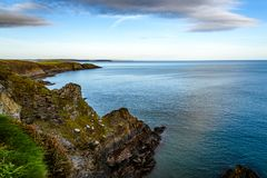 Scenic view of cliffs in Irish coast at sunset. Scenic view of cliffs in  Old Head of Kinsale peninsula in Ireland with green hills at sunset Royalty Free Stock Photography